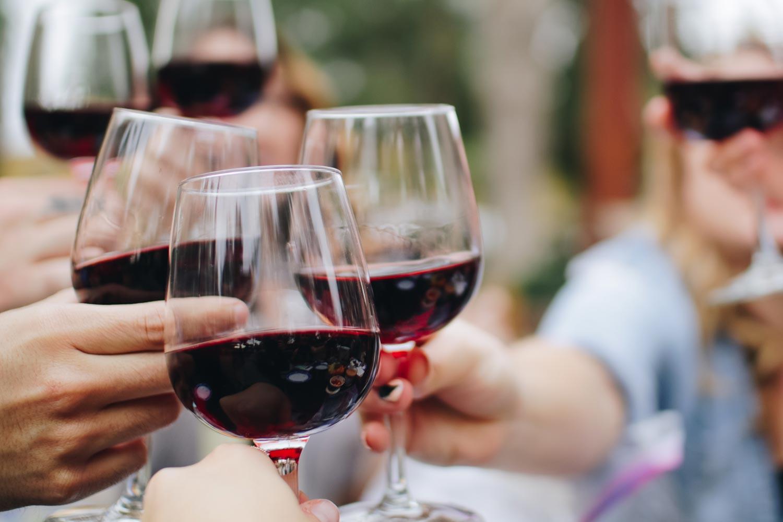 Rotwein-Gläser stoßen bei einer Weinverkostung an
