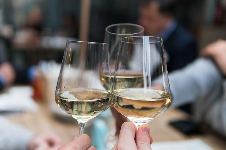 Weißwein in Gläsern, die bei Verkostung anstoßen