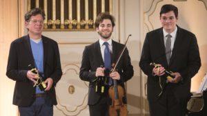 Franzobel und zwei weitere Künstler halten das Köchl Verzeichnis in den Händen