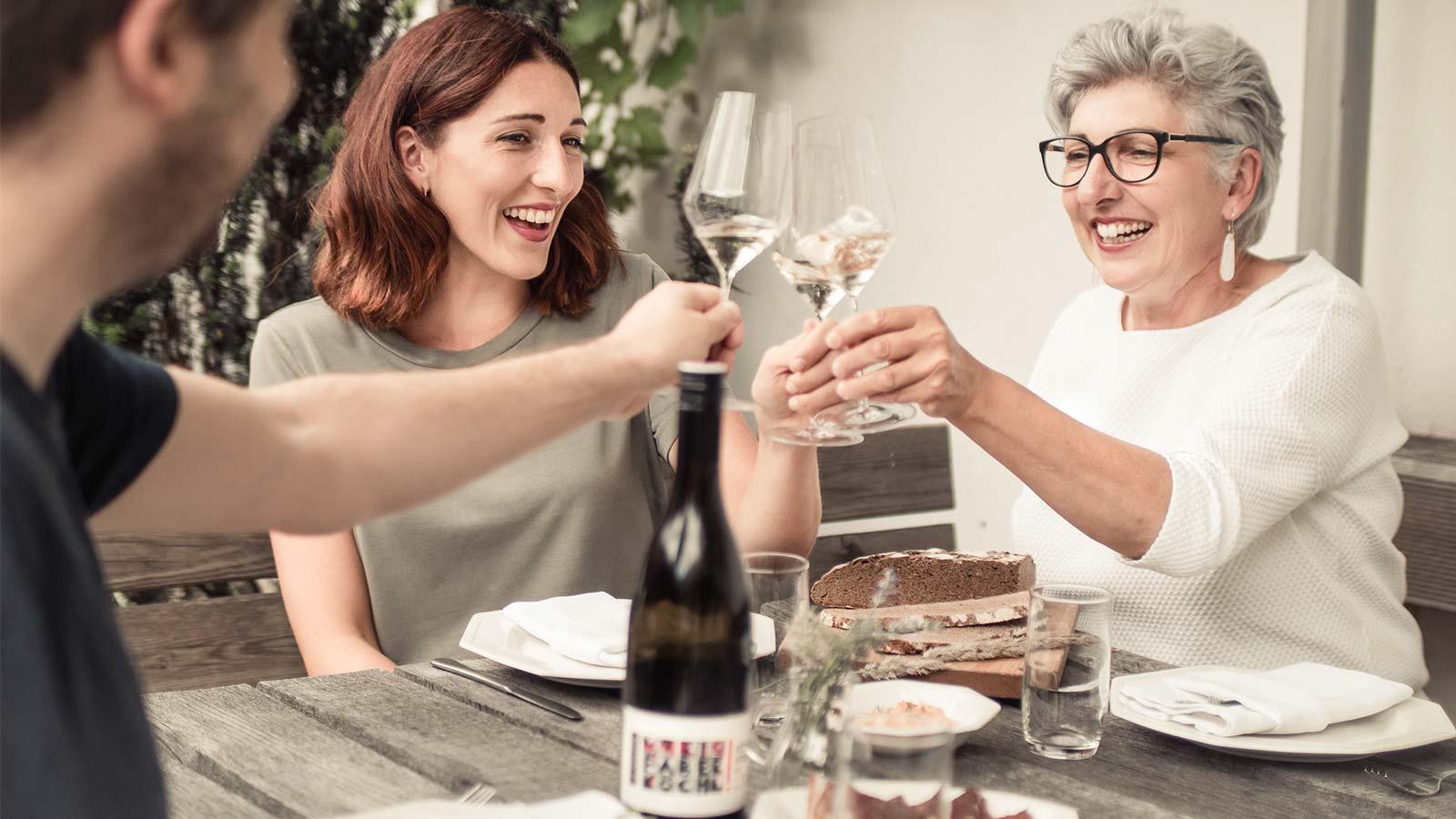 Anna Faber und Maria Faber-Köchl trinken Wein mit einem Gast
