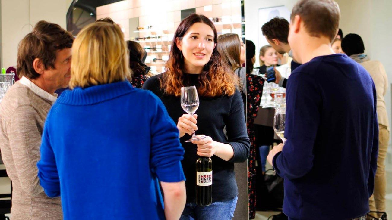 Anna Faber bei einer Verkostung mit einer Flasche Faber-Köchl-Wein