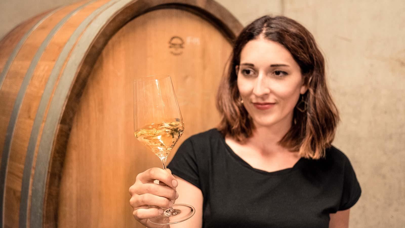 Anna Faber schwenkt ein Glas Weißwein vor einem Weinfass