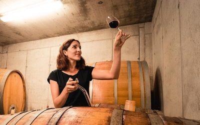 Anna Faber blickt auf ein Rotwein-Glas im Weinkeller