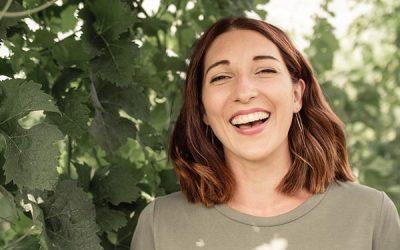 Portraitfoto von Anna Faber lachend im Weingarten
