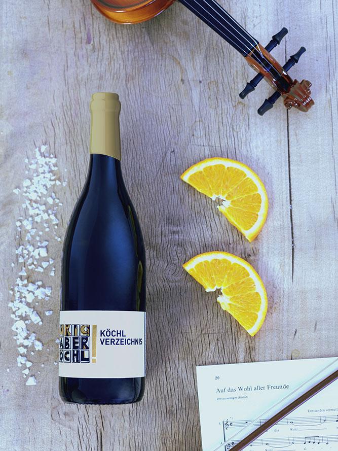Eine Flasche Köchl Verzeichnis Exklusiv Weiss mit einer Geige, Orangen und Salz