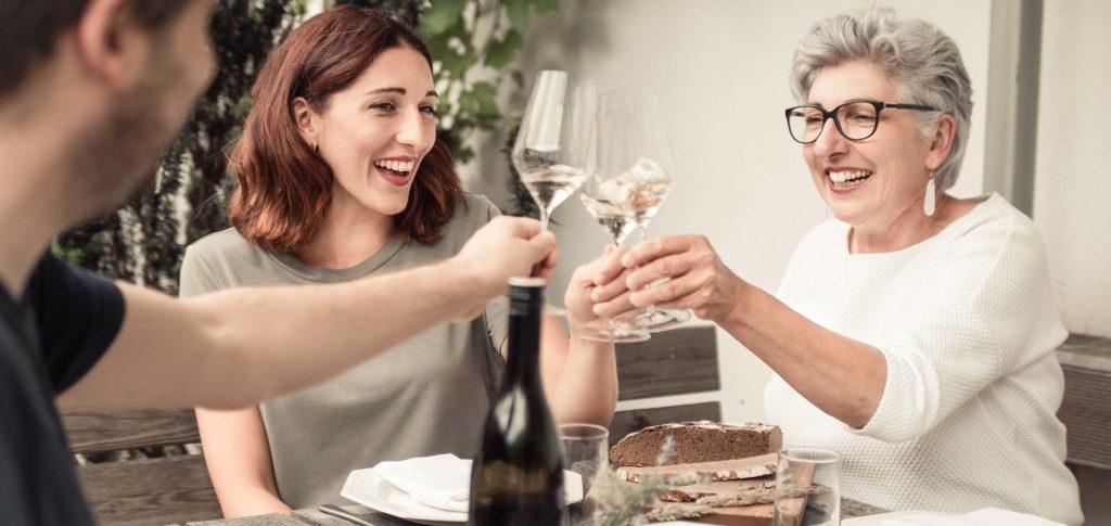 Winzerinnen Maria Faber-Köchl und Anna Faber verkosten Wein mit einem Gast
