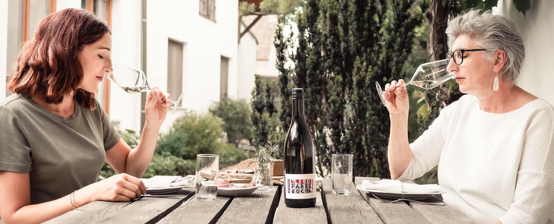 Anna Faber und Maria Faber-Köchl riechen an Glas Wein