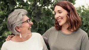 Maria Faber-Köchl und Anna Faber lachen vor einer Laubwand im Weingarten