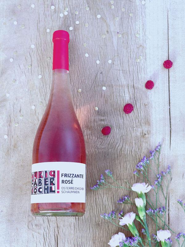 Flasche Frizzante Rosé vom Weingut Faber-Köchl auf Holzhintergrund mit Verzierung
