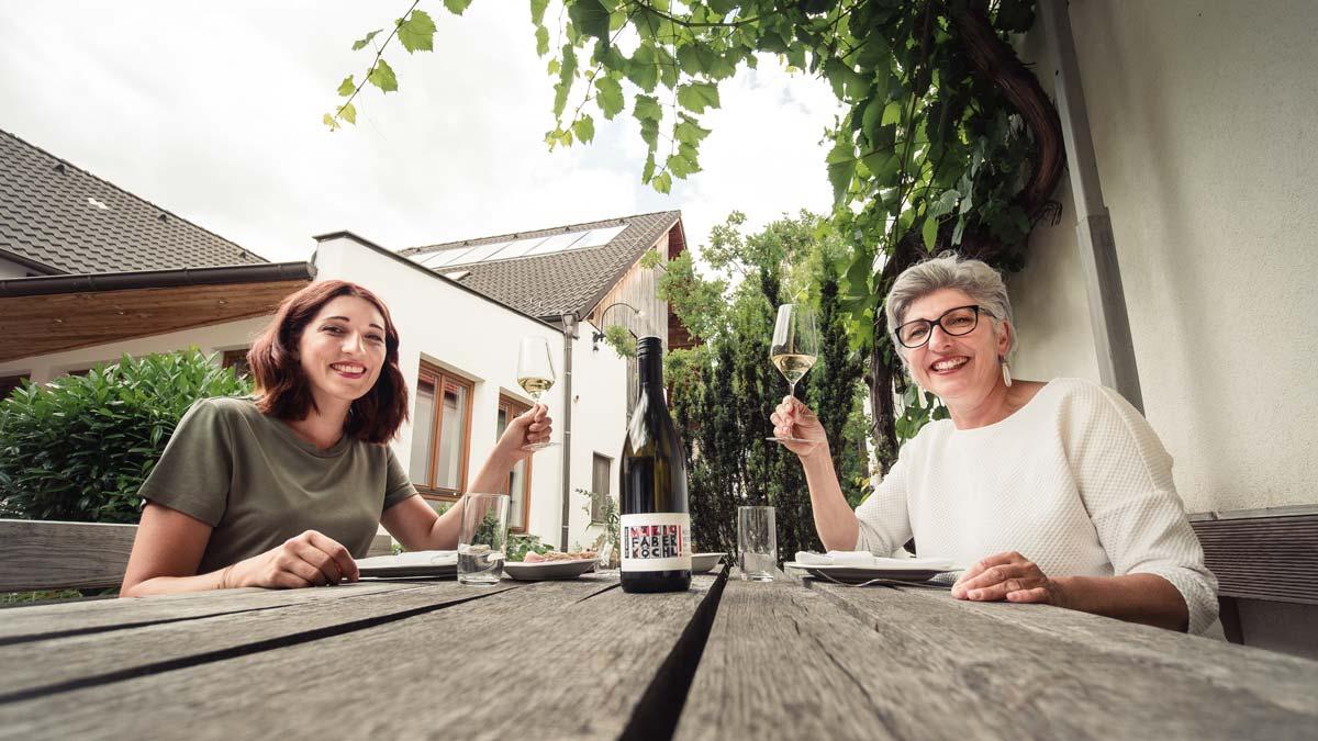 Anna Faber und Maria Faber-Köchl sitzen auf einem Holztisch, halten ein Glas Wein in der Hand und lachen in die Kamera.