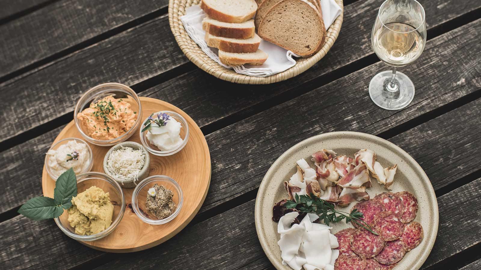 Turopoljeteller, Aufstriche, Brot und ein Glas Wein stehen auf einem Holztisch