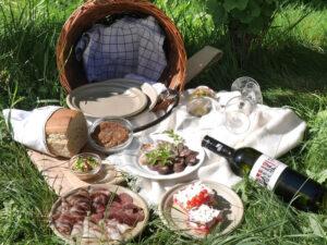 Ein Picknick-Korb des Weinguts Faber-Köchl in einer Wiese mit einer Flasche Wein, Schinken und Speck vom Turopoljeschwein, ein Faschiertes Laibchen, selbstgemachtes Brot und Ribiselschaumkuchen.
